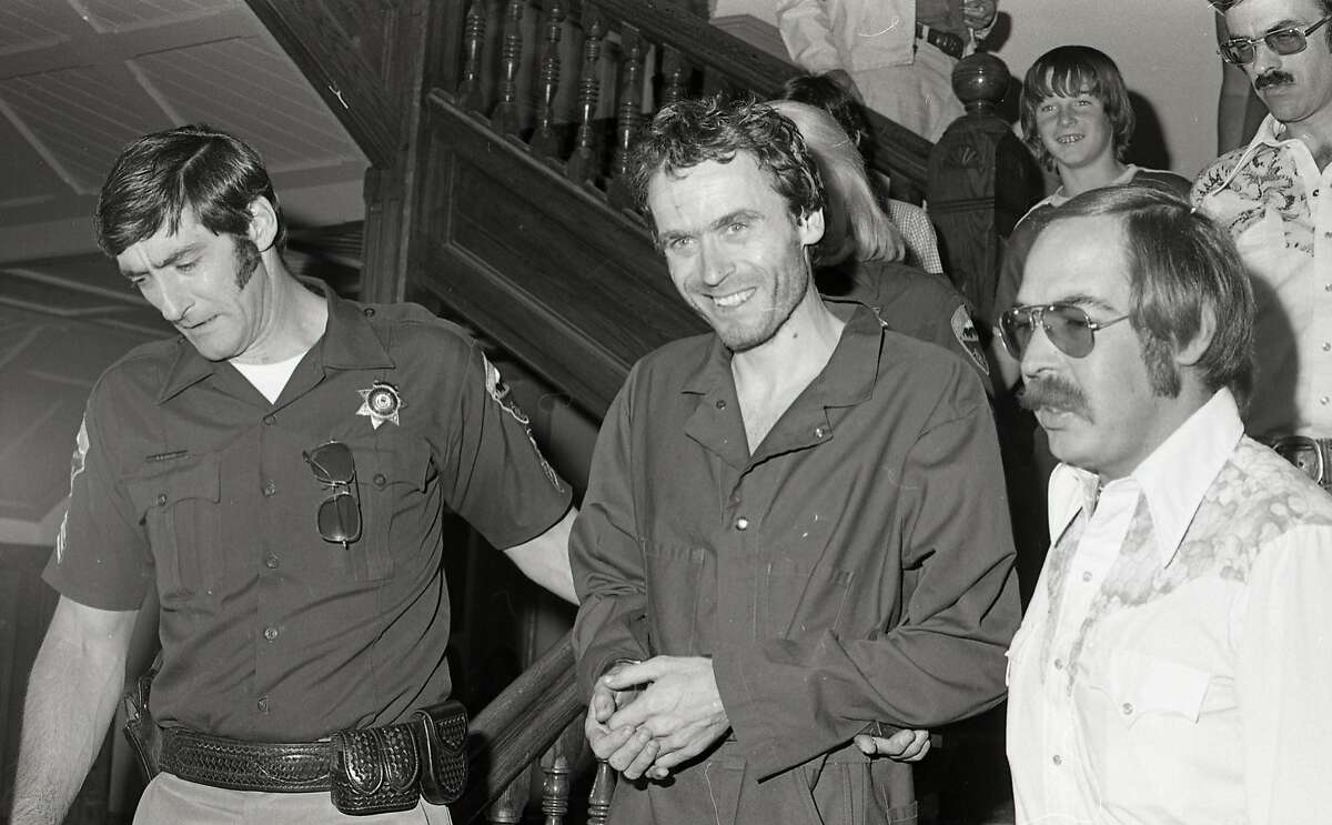 In this 1977 photo serial killer Ted Bundy, center, is escorted out of court in Pitkin County, Colo. The Glenwood Springs Post-Independent discovered the 40-year-old photo of Bundy, along with others, that had been locked in an old safe in the newsroom, which a local locksmith volunteered to open. The photos show Bundy in custody in 1977, the year he escaped from local law enforcement twice while awaiting a murder trial. (Glenwood Springs Post Independent via AP)