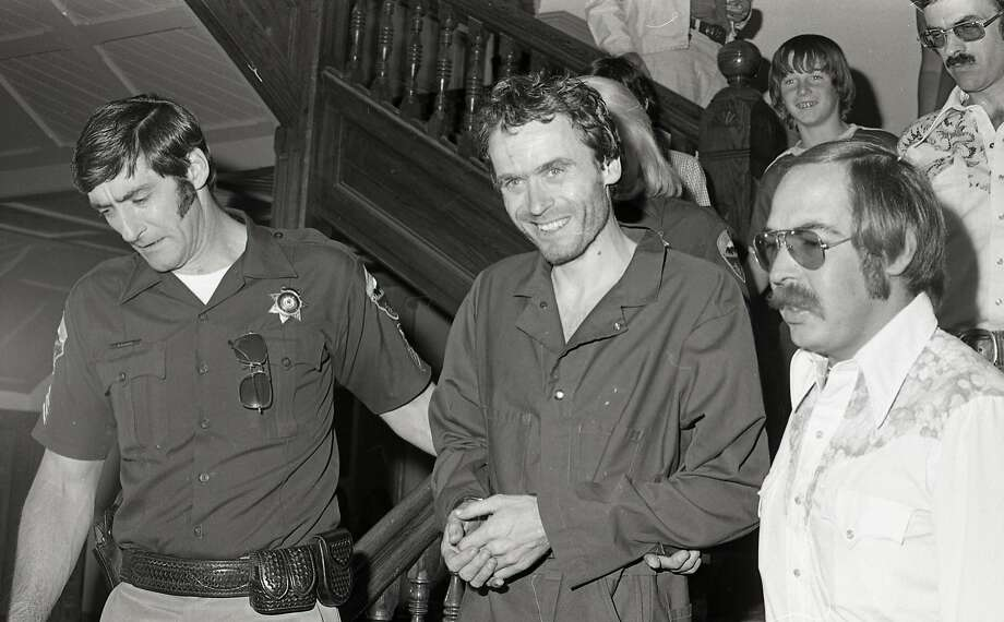In this 1977 photo serial killer Ted Bundy, center, is escorted out of court in Pitkin County, Colo. The Glenwood Springs Post-Independent discovered the 40-year-old photo of Bundy, along with others, that had been locked in an old safe in the newsroom, which a local locksmith volunteered to open. The photos show Bundy in custody in 1977, the year he escaped from local law enforcement twice while awaiting a murder trial. (Glenwood Springs Post Independent via AP) Photo: Associated Press
