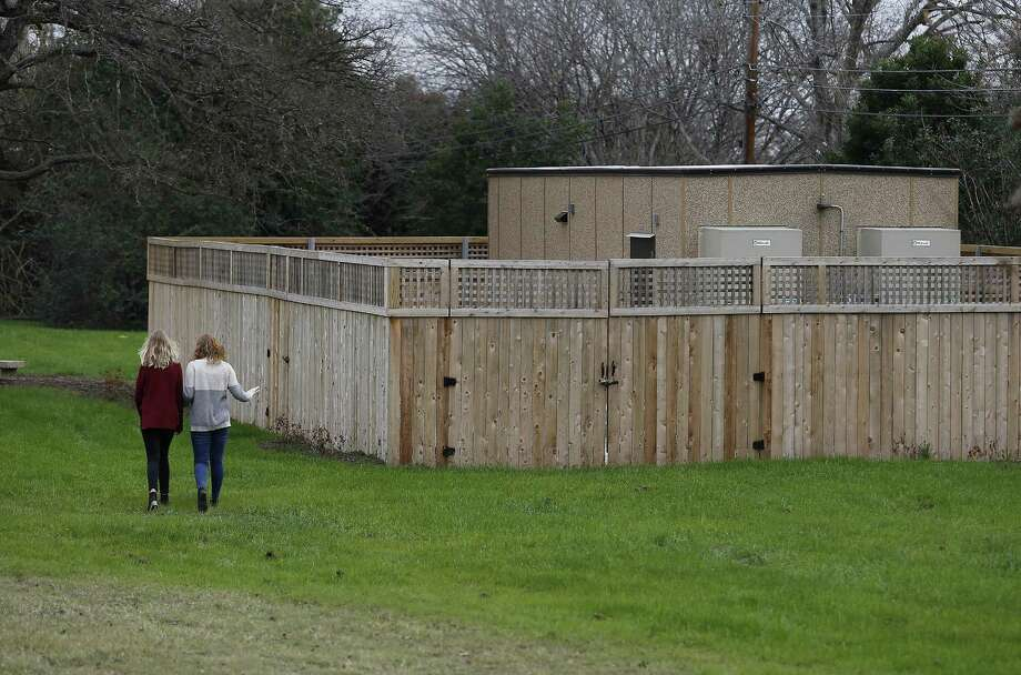 Siblings Anna (left) and Erin Franklin walk by a Google Hut in Haskin Park on Wednesday, Jan. 4, 2017. Their mother and Oak Park Northwood Homeowners Association member Cynthia Franklin is disappointed by the location of the Google Hut which was placed in Haskin Park near her home. She used to be able to look past her chain-link fence and see her kids playing on a playscape in the little park. Now, however, the hut blocks her view. She and others like fellow homeowner John Whitsett are upset and say the city violated its own ordinances in allowing Google to install the network building there. Among other things, they say, it violates rules about fencing, noise and construction. (Kin Man Hui/San Antonio Express-News) Photo: Kin Man Hui, Staff / San Antonio Express-News / ©2017 San Antonio Express-News