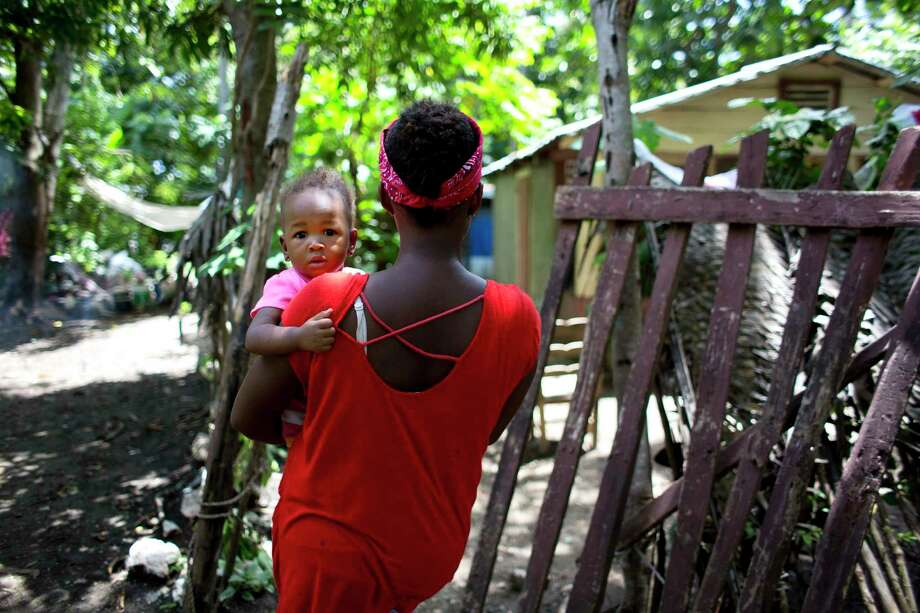 Janila Jean, 18, carries her daughter as she walks to her friend's house before an interview in Jacmel, Haiti. Jean said she was a 16-year-old virgin when a U.N. peacekeeper from Brazil raped her and left her pregnant. Photo: Dieu Nalio Chery, STR / Copyright 2016 The Associated Press. All rights reserved. This material may not be published, broadcast, rewritten or redistribu