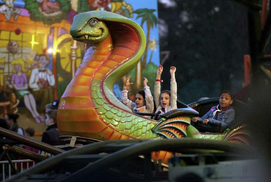 Ania Lawrence, 5, in center, and her friend Valerie Meyerovich, 8, both of Trumbull, ride the Cobra during the Rotary Club of Trumbull's 29th annual carnival at Hillcrest Middle School in Trumbull, Conn., on Tuesday Apr. 11, 2017. The carnival, which runs Friday from 6pm to 10 pm and again on Saturday from 1 p.m. to 10 p.m.,  features a range of amusement rides and games. You can purchase tickets for individual rides or buy an all-day bracelet for $25. Money raised is given out in the form of scholarships to Trumbull High School seniors. Photo: Christian Abraham / Hearst Connecticut Media / Connecticut Post
