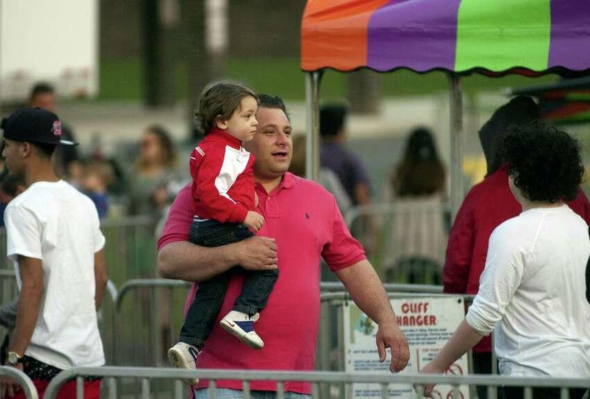Antonio Silveira, of Shelton, carries his son Aiden, 2, as they enjoy the Rotary Club of Trumbull's 29th annual carnival at Hillcrest Middle School in Trumbull, Conn., on Tuesday Apr. 11, 2017. The carnival, which runs Friday from 6pm to 10 pm and again on Saturday from 1 p.m. to 10 p.m., features a range of amusement rides and games. You can purchase tickets for individual rides or buy an all-day bracelet for $25. Money raised is given out in the form of scholarships to Trumbull High School seniors.
