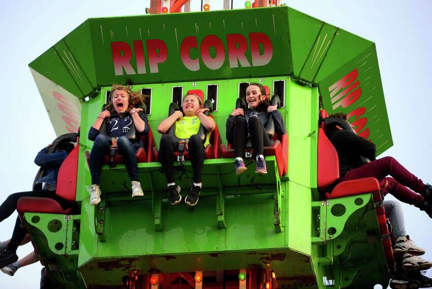 Claudia Hepfer, 12, of Trumbull, at left, Rachel Bikofsky, 12, in center, and a third friend who wished not be identified, ride on the Ripcord during the Rotary Club of Trumbull's 29th annual carnival at Hillcrest Middle School in Trumbull, Conn., on Tuesday Apr. 11, 2017. The carnival, which runs Friday from 6pm to 10 pm and again on Saturday from 1 p.m. to 10 p.m., features a range of amusement rides and games. You can purchase tickets for individual rides or buy an all-day bracelet for $25. Money raised is given out in the form of scholarships to Trumbull High School seniors.