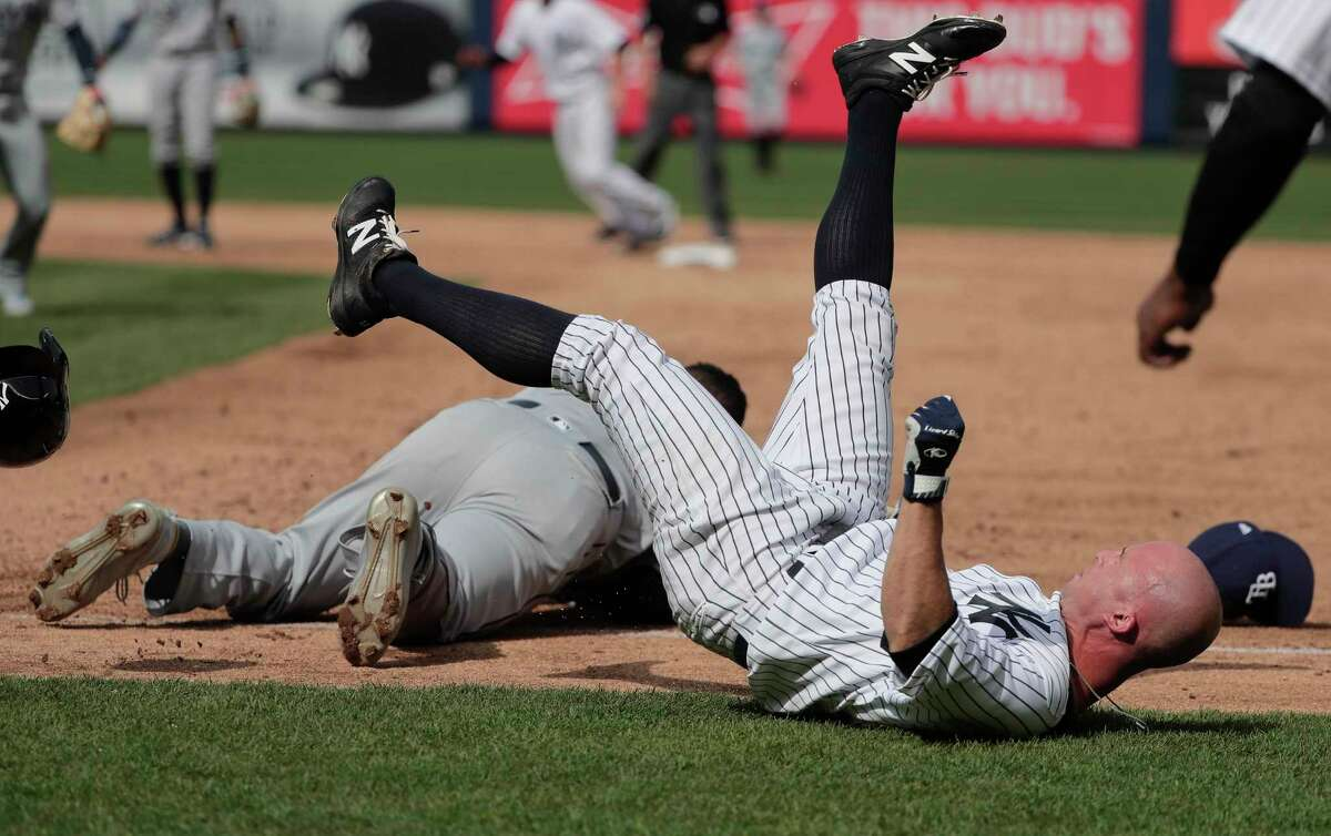New York Yankees' Brett Gardner, right, falls to the ground after colliding with Tampa Bay Rays first baseman Rickie Weeks after Weeks reached for an errant throw by pitcher Xavier Cedeno during the sixth inning of a baseball game, Wednesday, April 12, 2017, in New York. Chase Headley scored on the play. Both Weeks and Gardner left the game. (AP Photo/Julie Jacobson) ORG XMIT: NYJJ113