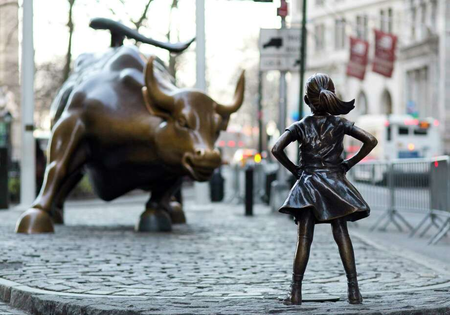 In this March 22, 2017 photo, the Charging Bull and Fearless Girl statues are sit on Lower Broadway in New York. Since 1989 the bronze bull has stood in New York City's financial district as an image of the might and hard-charging spirit of Wall Street. But the installation of the bold girl defiantly standing in the bull's path has transformed the meaning of one of New York's best-known public artworks. Pressure is mounting on the city to let the Fearless Girl stay. (AP Photo/Mark Lennihan) ORG XMIT: NYML101 Photo: Mark Lennihan / Copyright 2017 The Associated Press. All rights reserved.