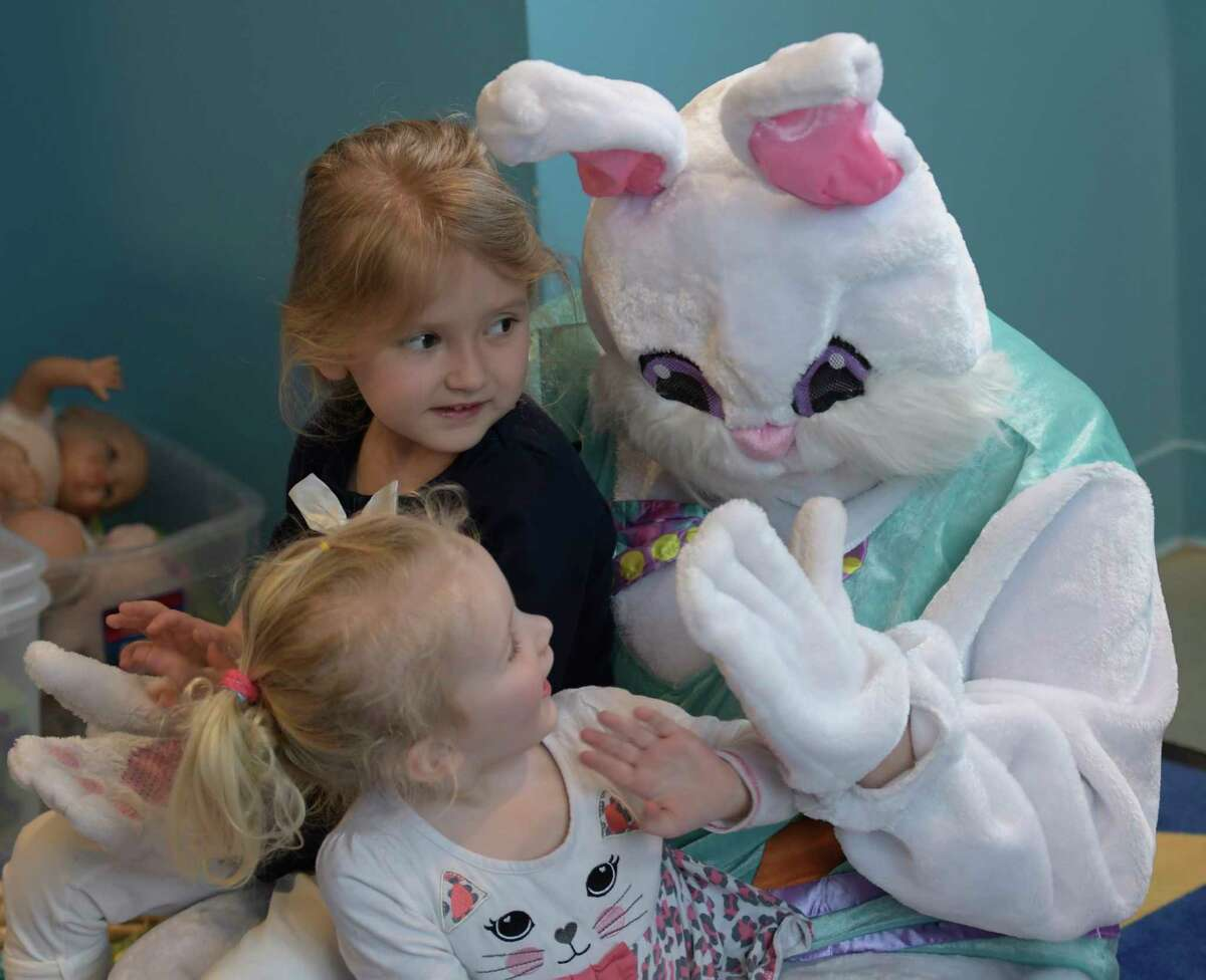 The Spring Bunny played by Katheryn Capalbo gets a high five from two year old Taylor Ketcham as her sister Colby 4, watches during class time at the Unity Sunshine III pre-school at the YWCA Wednesday April 12, 2017 in Troy, N.Y. (Skip Dickstein/Times Union)