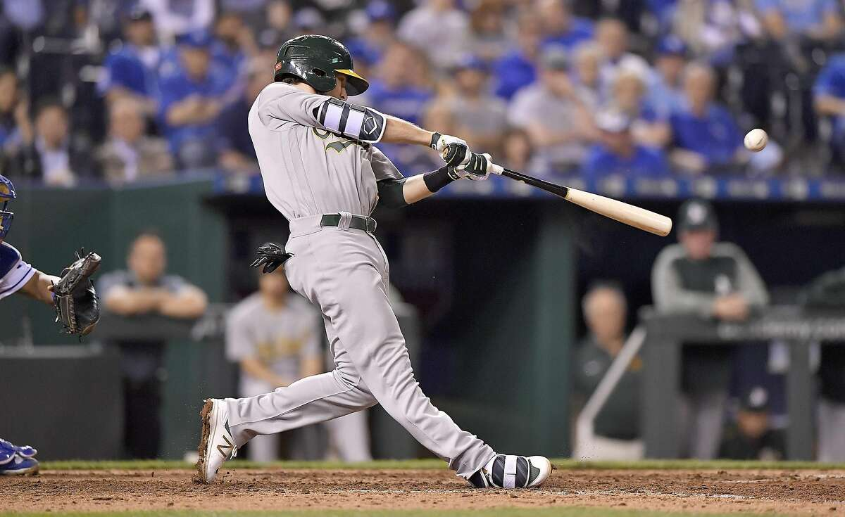 The Oakland Athletics' Jed Lowrie connects on a two-run double in the sixth inning against the Kansas City Royals at Kauffman Stadium in Kansas City, Mo., on Wednesday, April 12, 2017. (John Sleezer/Kansas City Star/TNS)