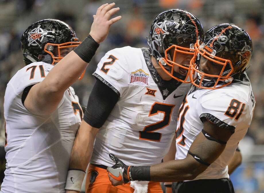 Oklahoma State players Jhajuan Seales (81) celebrates a touchdown with quarterback Mason Rudolph (2) and center Brad Lundblade during the second half of the Alamo Bowl, Thursday, Dec. 29, 2016, at the Alamodome in San Antonio. Oklahoma State beat Colorado 38-8. (Darren Abate/For the Express-News) Photo: Darren Abate/San Antonio Express-News