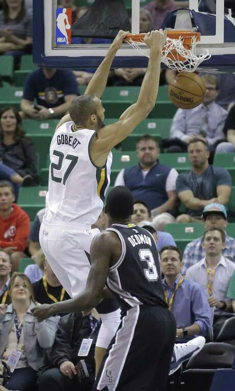 Jazz center Rudy Gobert dunks as Dewayne Dedmon looks on during the first half in Salt Lake City. The Spurs open the playoffs Saturday against Memphis. Photo: Rick Bowmer / Associated Press / Copyright 2017 The Associated Press. All rights reserved.