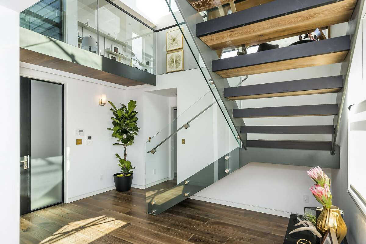 The foyer features frosted glass, a hardwood floor, and an architectural staircase with floating tread.