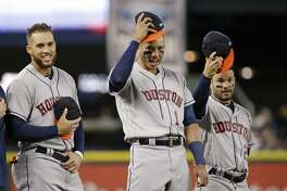 Houston Astros' Jose Altuve, right, and Carlos Correa, tip their caps as George Springer looks on after the national anthem before a baseball game against the Seattle Mariners Wednesday, April 12, 2017, in Seattle. (AP Photo/Elaine Thompson)