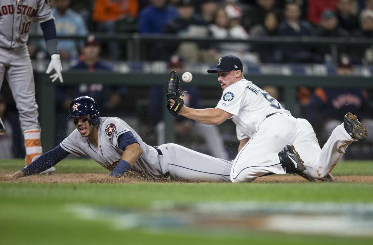 SEATTLE, WA - APRIL 12: Relief pitcher Dan Altavilla #53 of the Seattle Mariners juggles the baseball as Carlos Correa #1 of the Houston Astros slides safely into home plate after a wild pitch during the seventh inning of a game at Safeco Field on April 12, 2017 in Seattle, Washington. (Photo by Stephen Brashear/Getty Images)