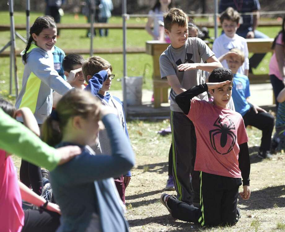 Julian Curtiss School fifth graders Jake Romancello, left, and Christian Hincapie participate in the captain on deck team building game during Greenwich Public Schools' Orienteering Adventure Days at the Camp Seton Scout Reservation in Greenwich, Conn. Tuesday, April 19, 2016. Led by P.E. teachers and staff from Camp Seton Scout Reservation, all fifth graders from the eleven Greenwich Public Elementary Schools meet and interact with those students who will be in their sixth grade classes next year while participating in a variety of activities blending fitness, writing, map reading, and team building skills. Photo: Tyler Sizemore / Hearst Connecticut Media / Greenwich Time