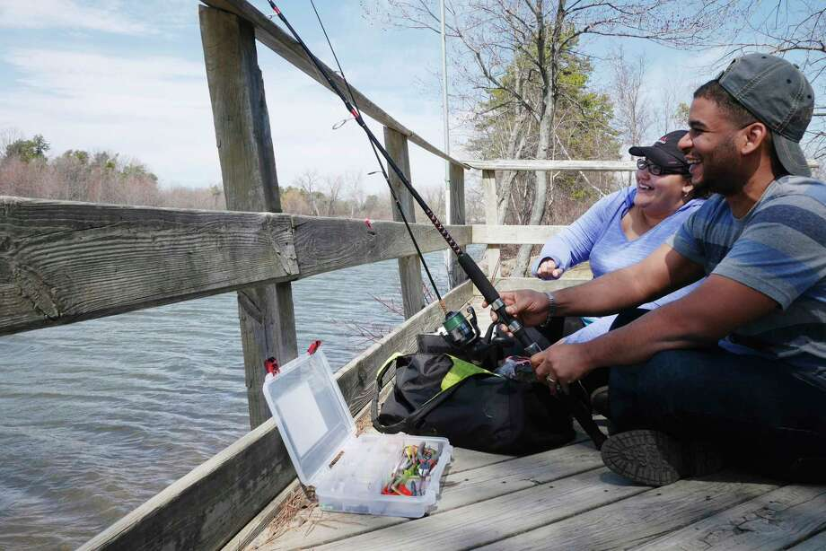 Dashira Familia, left, and her husband, Jean Carlos Familia of Cohoes, enjoy the warm temperatures and the fishing at Rensselaer Lake on Monday, April 10, 2017, in Albany, N.Y.      (Paul Buckowski / Times Union) Photo: STAFF / 20040201A