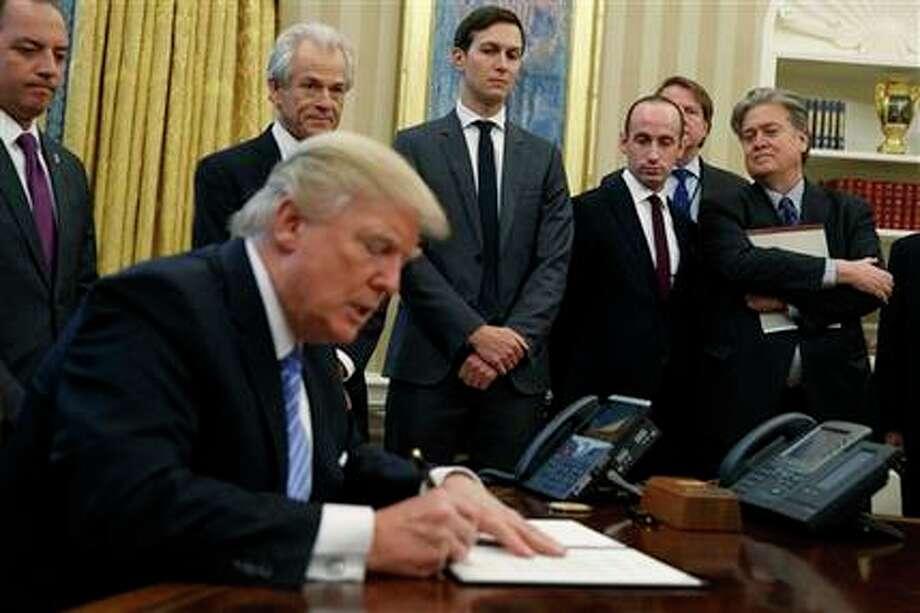 En esta imagen del 23 de enero de 2017, el estratega de la Casa Blanca Steve Bannon, a la derecha, observa con otras personas mientras el presidente de Estados Unidos, Donald Trump, firma un decreto en la Oficina Oval de la Casa Blanca en Washington. (AP Foto/Evan Vucci, Archivo)