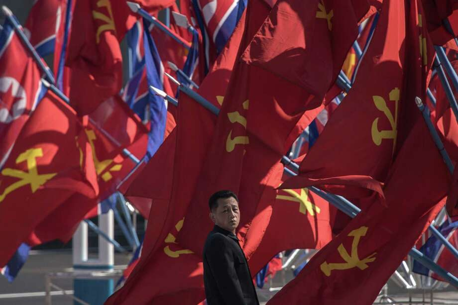 A man stands before flags as North Korea's leader Kim Jong-Un arrives for the opening ceremony for the Ryomyong Street housing development in Pyongyang on April 13, 2017. Completion of the sprawling Ryomyong Street development, just down a wide avenue from the mausoleum where Kim Jong-Un's grandfather Kim Il-Sung and father Kim Jong-Il lie in state, was repeatedly promised in time for the 105th anniversary of the birth of the North's founder. / AFP PHOTO / Ed JONESED JONES/AFP/Getty Images Photo: ED JONES, Staff / AFP/Getty Images / AFP or licensors