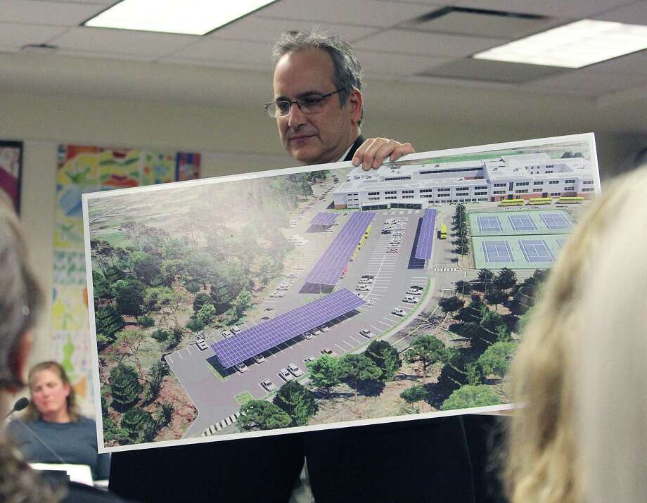 Fairfield Public Schools Manager of Construction, Security and Safety Sal Morabito shows designs for carports in Ludlowe and Warde high school parking lots at the April 6, 2017 Board of Education meeting in Fairfield, Conn. Photo: Laura Weiss / Hearst Connecticut Media / Fairfield Citizen