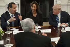 """(FILES) This file photo taken on February 9, 2017 shows US President Donald Trump speaking during a meeting with airline industry executives, including Oscar Munoz (L), President and CEO of United Airlines; and Deborah Flint (C), CEO of Los Angeles World Airports (LAWA), in the State Dining Room of the White House in Washington, DC. United Continental chief executive Oscar Munoz said April 12, 2017he would not resign, and he again apologized for forcibly removing a customer from an overbooked flight. Munoz was asked about calls for his resignation as leader of the embattled airline on the ABC show """"Good Morning America"""" following widespread outrage at the company's actions in the incident Sunday.""""I was hired to make United better and we've been doing that and that's what I'll continue to do,"""" Munoz said.  / AFP PHOTO / SAUL LOEBSAUL LOEB/AFP/Getty Images"""