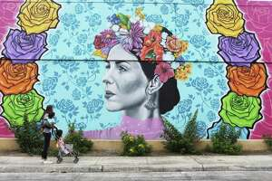 """Childcare provider Kristin Nielsen walks with her young charges by a mural on a wall at the Fiesta Store on Broadway earlier this week. The mural was commissioned by Red Bull and created by Los Otros Murals. A contest was held and participants were able to enter their Fiesta-theme photographs with the winner to be used as the basis for the mural. Los Otros Murals' are artist Nik Soupe and David """"Shek"""" Vega."""