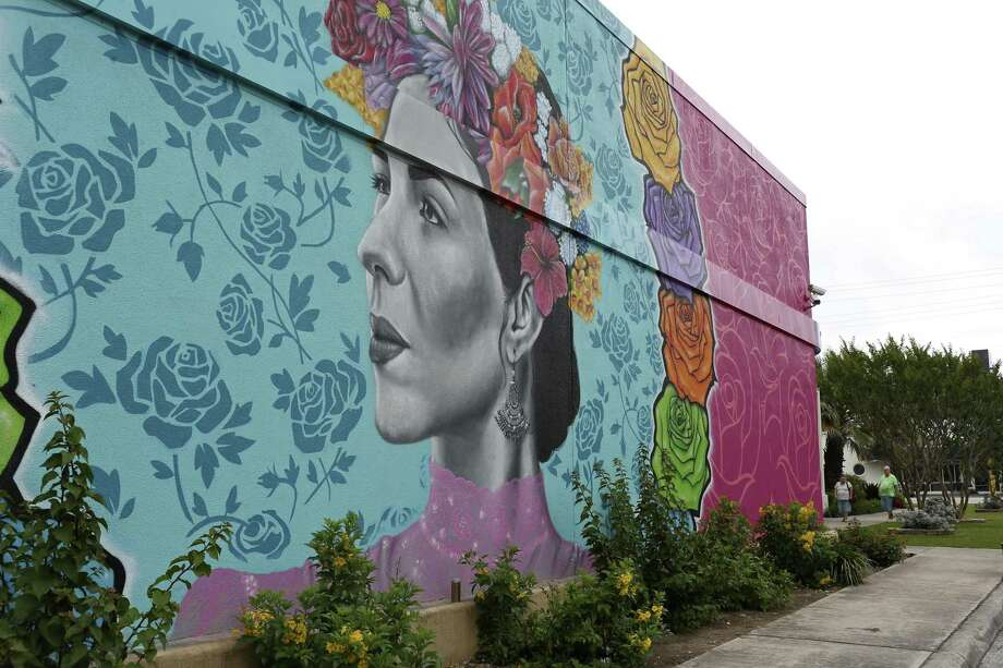 "Childcare provider Kristin Nielsen walks with her young charges by a mural on a wall at the Fiesta Store on Broadway earlier this week. The mural was commissioned by Red Bull and created by Los Otros Murals. A contest was held and participants were able to enter their Fiesta-theme photographs with the winner to be used as the basis for the mural. Los Otros Murals' are artist Nik Soupe and David ""Shek"" Vega. Photo: Jerry Lara /San Antonio Express-News / © 2017 San Antonio Express-News"