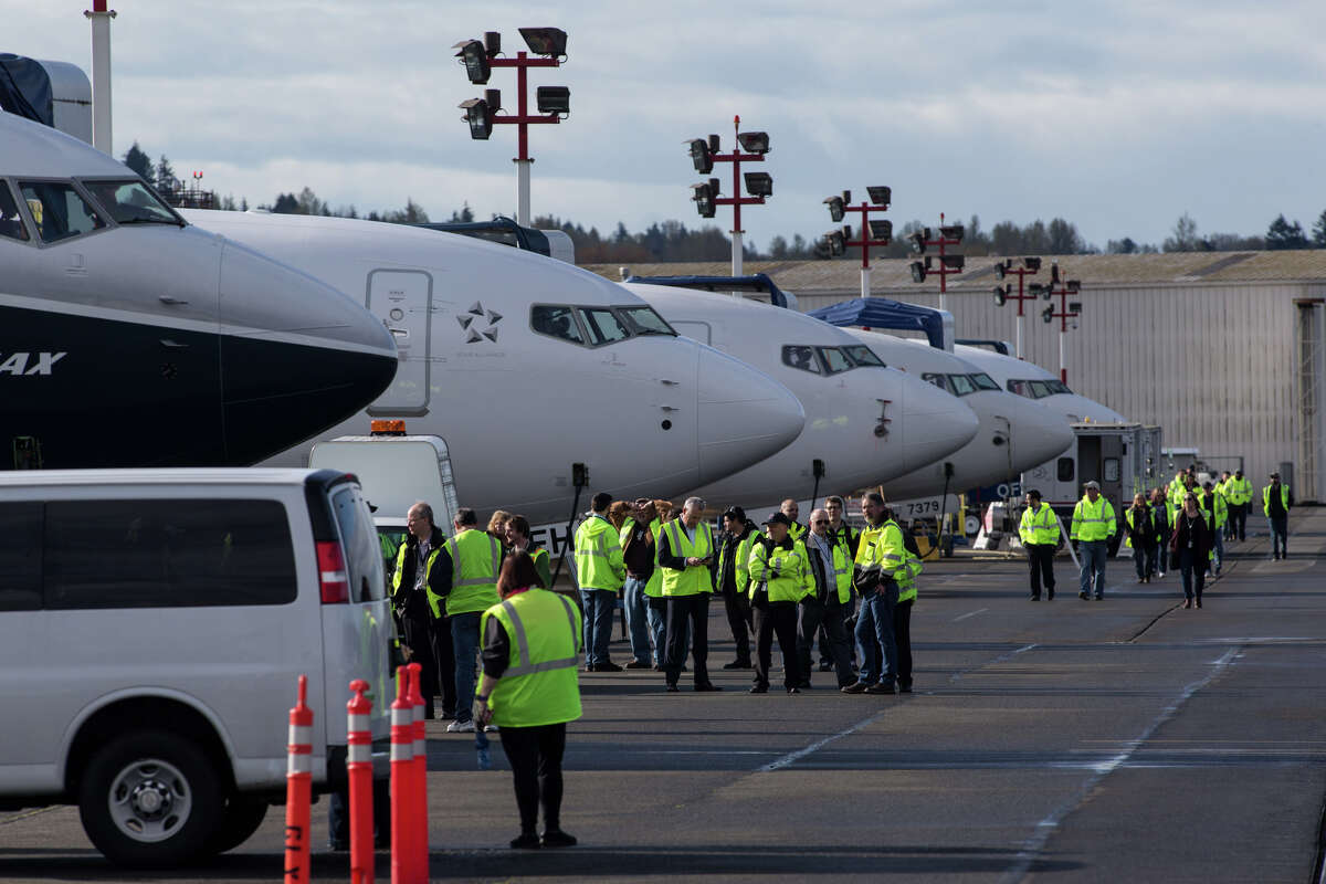 Boeing employees wait near the 737 Max 9, left, in a row of other 737's, before the Max 9's first test flight, in Renton on Thursday, April 13, 2017.