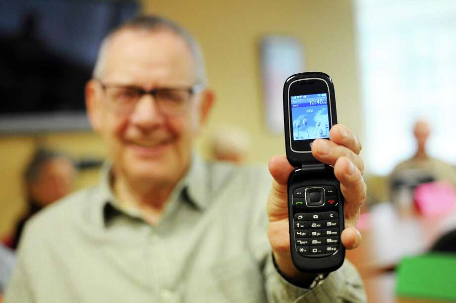 Tom Gale, 81, holds the flip phone he uses daily inside the Stamford Senior Center in downtown Stamford, Conn. on Wednesday, April 12, 2017. Photo: Michael Cummo / Hearst Connecticut Media / Stamford Advocate