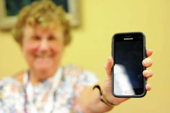 """Ellie Guss, 83, holds up the phone she uses daily inside the Stamford Senior Center in downtown Stamford, Conn. on Wednesday, April 12, 2017. Guss learned to text because her grandchildren """"won't pick up the phone."""""""