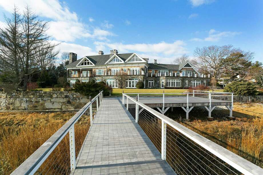 The gated waterfront estate at 5 Judy Point Lane has 275 feet of coastline, a private beach and deep water dock on Burritt Cove. Photo: /