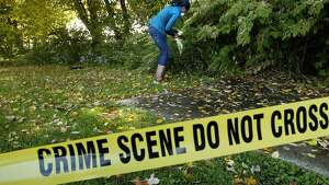 Shawnna Enoch gathers and bags evidence for Sara White's forensic science class at AITE in Stamford,Conn on Monday October 19,2009 at the crime scene White has created for her students.