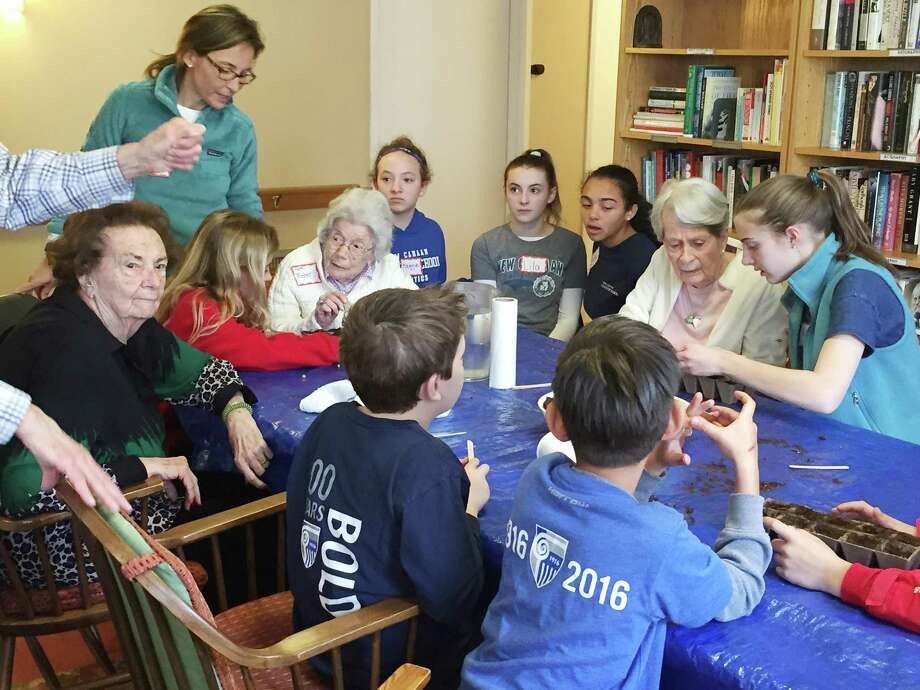 Students, their families and teachers from New Canaan Country School help seniors from Waveny Life Network's The Inn plant seedlings on April 1. Photo: Contributed Photo / New Canaan News