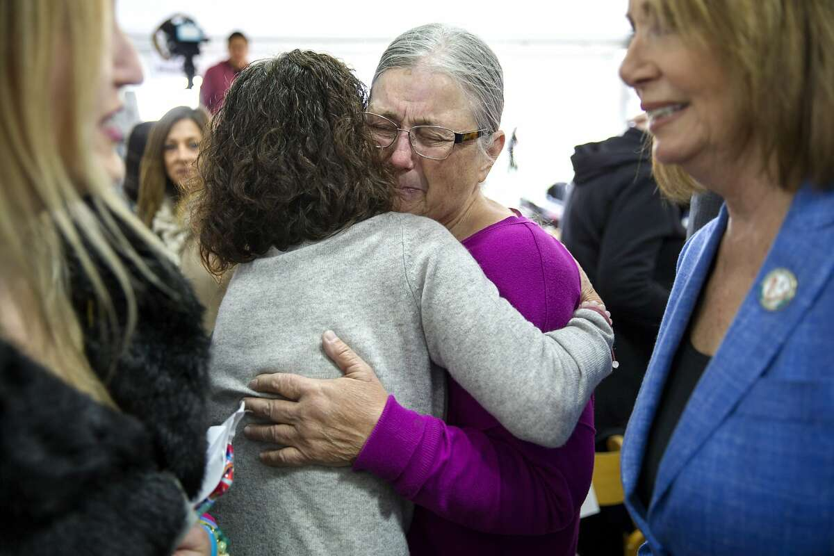 Sue Story (in purple) embraces Erika Brooks before a ceremony at the Golden Gate Bridge Welcome Center Plaza on Thursday, April 13, 2017, in San Francisco, Calif. The ceremony commemorated the beginning of the Golden Gate Bridge suicide deterrent system construction project. Sue's son Jacob died in 2010 after he jumped from the bridge. Erika's daughter Casey died in 2008 when she jumped off the bridge.
