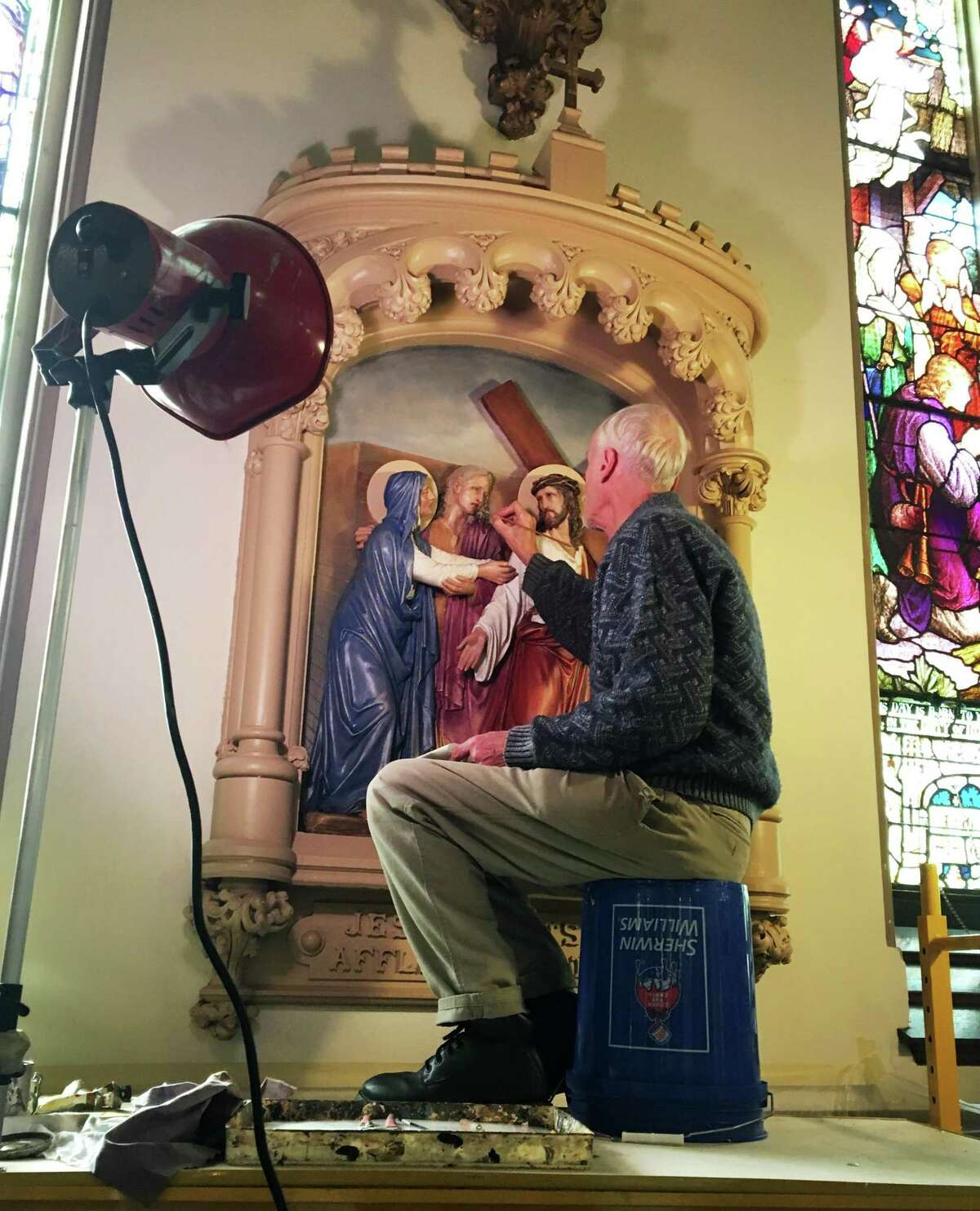 Henry Pospieszalski works on the the restoration of the Fourth Station, Jesus meets his mother. The 14 Stations of the Cross on the walls of the Church of Assumption in Ansonia, Conn. have been meticulously restored to their original luster.