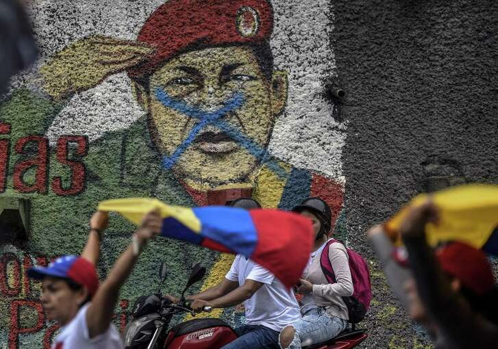Venezuelan opposition activists march during a protest against President Nicolas Maduro's government, in Caracas on April 13, 2017. A 32-year-old man died Thursday after being shot and wounded in a demonstration on April 11, becoming the fifth victim in the protests that began almost two weeks ago. Dozens of people have been injured and more than 100 arrested since April 6, according to authorities. / AFP PHOTO / JUAN BARRETOJUAN BARRETO/AFP/Getty Images