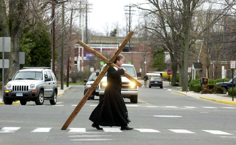 The Rev. Christopher Leighton, of St. Paul's Episcopal  Church in Darien, takes a turn at carrying a cross as he joins a group of Darien residents and local clergy in a procession  down Boston Post Road in honor of Good Friday. Photo: Kathleen O'Rourke / Hearst Connecticut Media / SCNI
