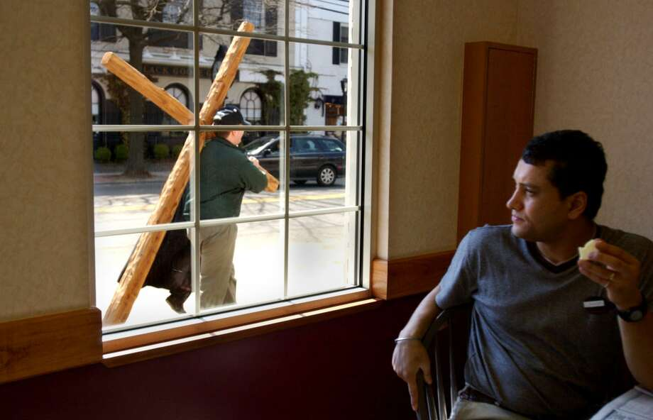 Sanjeev Singh takes a break from his shift at Dunkin Donuts and watches as members of different congregations process down the Post Road taking turns carrying a wooden cross to honor Good Friday. Kathleen O'Rourke/Staff photo Photo: / ST