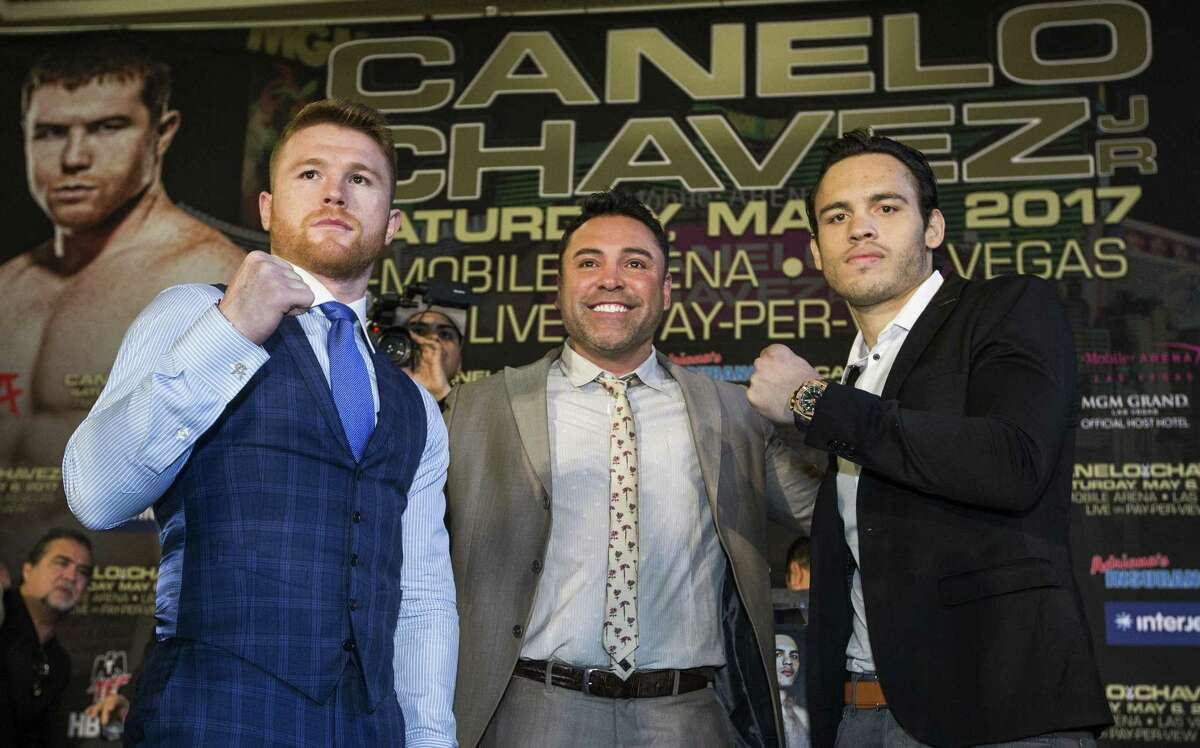 Canelo Alvarez (left) and Julio Cesar Chavez Jr., pose for photos with Oscar De La Hoya (center) during a news conference at Minute Maid Park in Houston on Feb. 23, 2017. The Mexican boxers are scheduled to fight May 6, 2017, at T-Mobile Arena in Las Vegas.