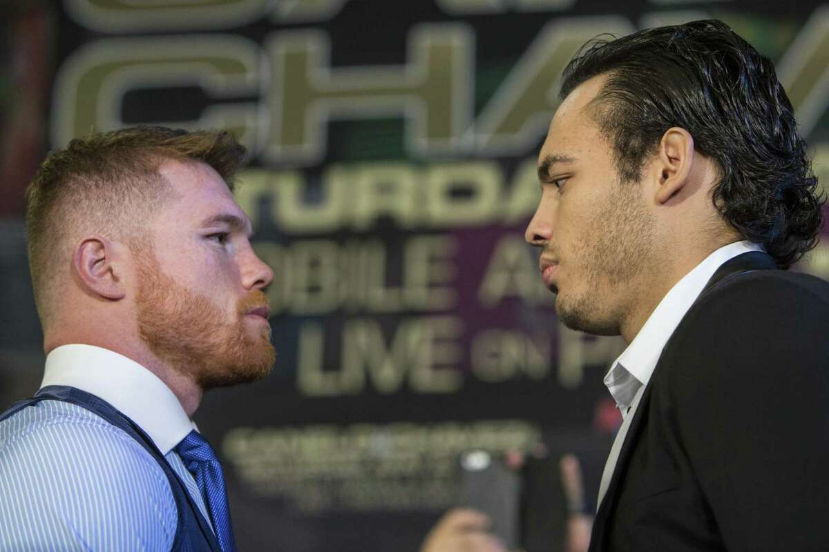 Canelo Alvarez (left) and Julio Cesar Chavez Jr. face off as they are introduced during a promotional news conference at Minute Maid Park on Feb. 23, 2017, in Houston.