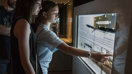 Samantha Merrill, 14, and Grace Ross, 14, visiting from Beaumont, look at an interactive touchscreen in the Jim Bowie exhibit at the Alamo April, 7. These kiosks house artifacts and feature screens that use translucent touchscreen technology allowing patrons to click the screen for detailed information.