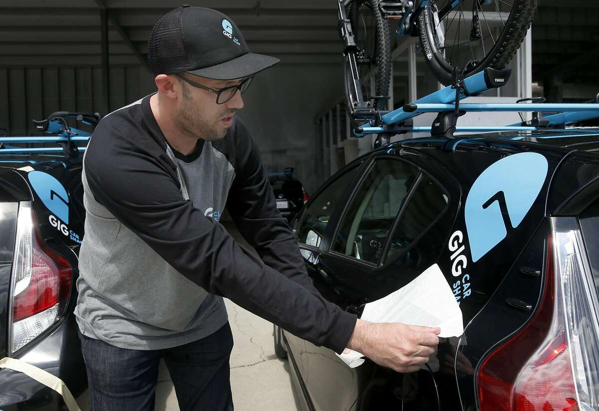 Fleet manager Tor Larsen removes the backing from a Gig logo on a car share vehicle at a AAA storage yard in Oakland, Calif. on Thursday, April 13, 2017. The fleet of 250 Priuses, each with two bike racks mounted to the roof, takes to the streets of Berkeley and Oakland on April 30, when the automobile club's car sharing service launches.
