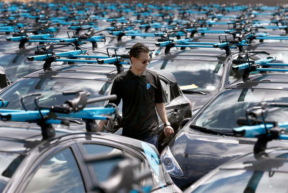 Head of operations Edmund Solis walks among Gig vehicles at an Oakland storage yard. The service is expanding to include San Francisco airport. Photo: Paul Chinn, The Chronicle