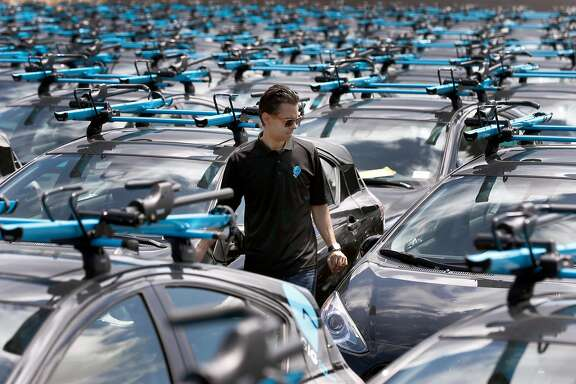 Head of operations Edmund Solis walks among the fleet of a Gig car share vehicles at a AAA storage yard in Oakland, Calif. on Thursday, April 13, 2017. The fleet of 250 Priuses, each with two bike racks mounted to the roof, takes to the streets of Berkeley and Oakland on April 30, when the automobile club's car sharing service launches.