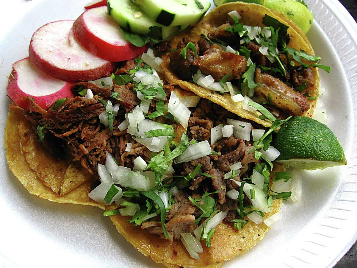 Clockwise from left: suadero, tripas and bistec tacos with lime, radishes, cucumber, cilantro and onions from Taquitos West Ave.