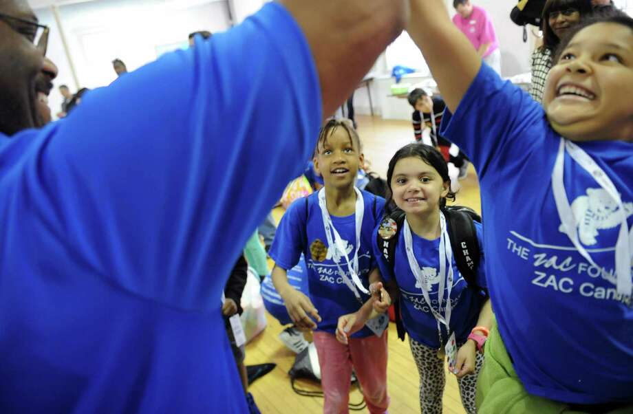 Third-graders Shaniah Euell, left, and Jailyn Bautista watch as Stephanie Alvarez high-fives Greenwich Boys & Girls Club CEO Bobby Walker Jr.during the ZAC Foundation swim camp closing ceremony at the Boys and Girls Club of Greenwich in Greenwich, Conn. Thursday, April 13, 2017. Children participated in the week-long ZAC Foundation swim camp at the Boys and Girls Club where they will spent time swimming in the pool while also learning important lessons about swimming safety. Karen and Brian Cohn founded The ZAC Foundation in 2008 in honor of their 6-year-old son, Zachary, who died after his arm became entrapped in a pool drain. Photo: Tyler Sizemore / Hearst Connecticut Media / Greenwich Time