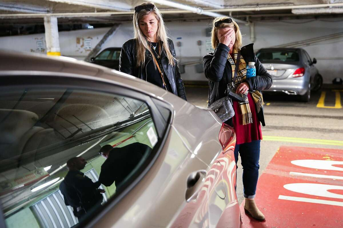 Julia Wilkinson (left), of Charlotte, North Carolina, and her mother Mary Wilkinson (right) stand by as police officers (reflected in the window) discuss their investigation into items stolen from their rental car at the Anchorage Square parking lot in San Francisco, California, on Thursday, April 13, 2017. The ashes of Joe Wilkinson, the father and husband to Julia and Mary were among many things that were stolen. Melanie Woodrow (not pictured), a television reporter at abc7 called a police commander which instigated a police investigation. Julia Wilkinson had planned to look for her fathers remains in pawn shops in the Haight but instead met with police officers at the scene of the crime near Fisherman's Wharf.