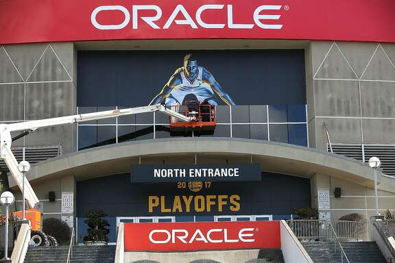 The Golden State Warriors 'Strength in Numbers' campaign begin to put up their signage on the north entrance of the Oracle Arena on Thursday, April 13, 2017, in Oakland, Calif.
