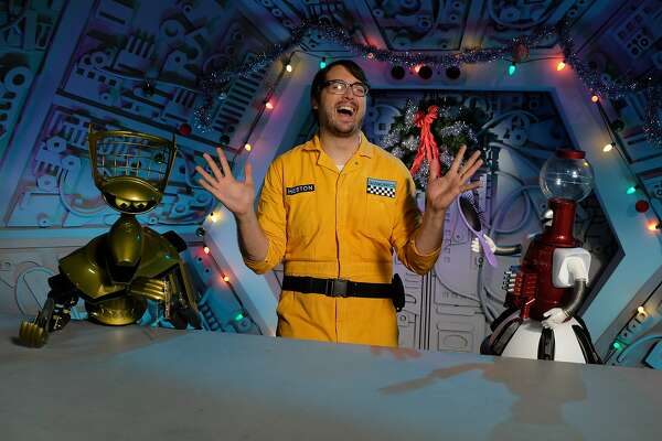 """Jonah (Jonah Ray of The Nerdist Podcast, center) is the new human test subject who's subjected to terrible movies in the new season of """"Mystery Science Theater 3000,"""" which launches April 14 on Netflix. At least Jonah has some familiar robot friends to help him -- Crow (left) and Tom Servo (right) from the original TV series."""