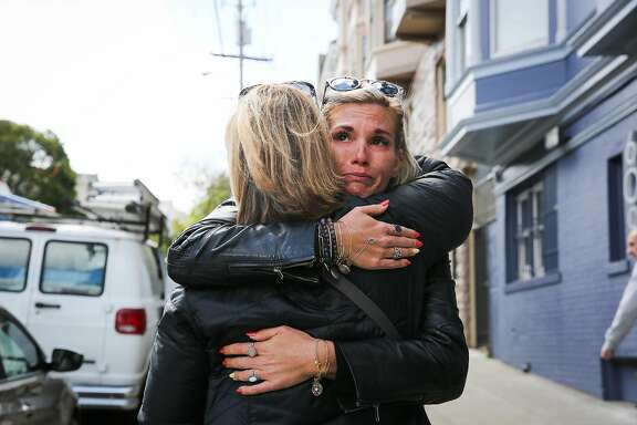 Julia Wilkinson (back), of Charlotte, North Carolina, hugs her mother Mary Wilkinson (front) a day after her father's ashes were stolen from their rental car on Wednesday afternoon in San Francisco, California, on Thursday, April 13, 2017.