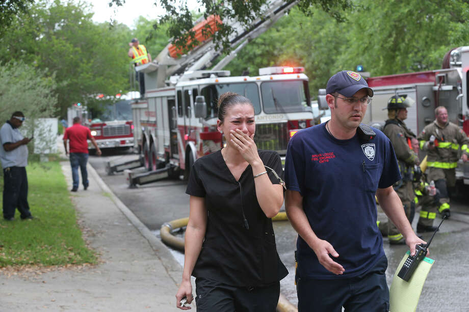 A woman arrives grief stricken as San Antonio firefighters extinguish a fire that gutted two homes Thursay April 13, 2017 on the 16,700 block of Crystal Glade on the city's North Side. Fire Chief Charles Hood said the fire started about 2:55 p.m. and the homes were engulfed with significant collapse possibilities. Arson will be investigating to determine the cause of the blaze. Hood said wind may have been a factor that caused the fire to spread to a secnd home. There were no injuries. Photo: John Davenport