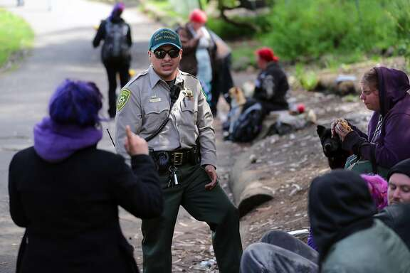 San Francisco Park Ranger Elmer Jimenez visits with a few visitors in Golden Gate Park during his patrol on Thurs. April 13, 2017, in San Francisco, Calif.