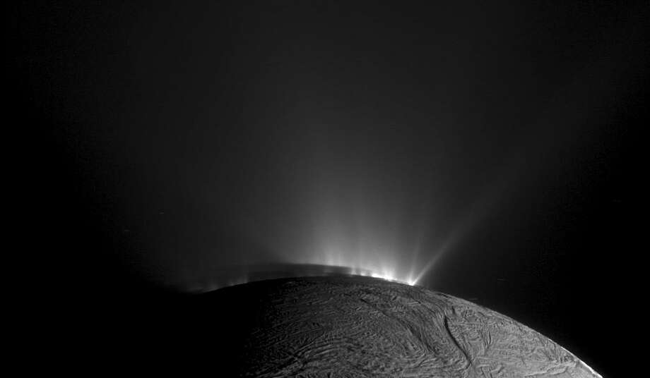 In an undated handout photo, rows of plumes rise from ice fractures on the surface of Enceladus, a moon orbiting Saturn. New findings from data collected by NASA's Cassini spacecraft suggest that icy moons like Enceladus could be the home to microbes or other life-forms. (NASA/JPL-Caltech/Space Science Institute via The New York Times) — FOR EDITORIAL USE ONLY Photo: NASA/JPL-CALTECH/SPACE SCIENCE INSTITUTE, HO / NYT / NASA/JPL-CALTECH/SPACE SCIENCE INSTITUTE